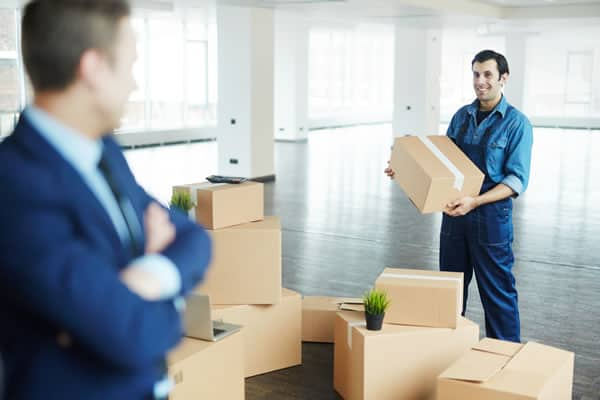 Mover and businessman with boxes in empty office