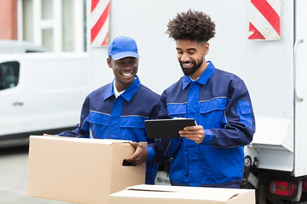 Two Delivery Men Looking At The Digital Tablet