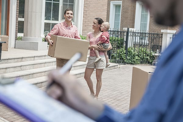 Mover holding clipboard and invoice, family in the background