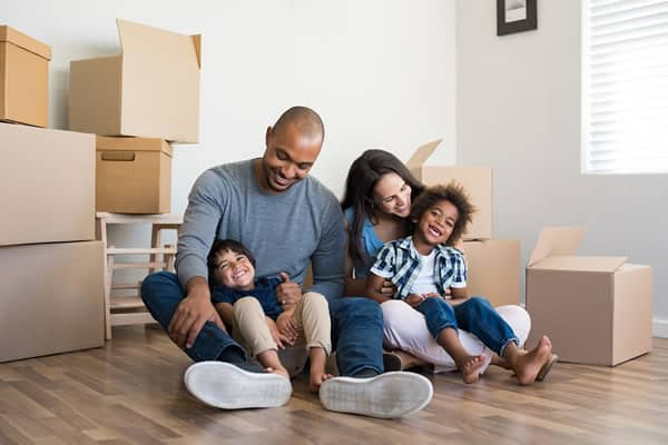 Smiling family surrounded by moving boxes