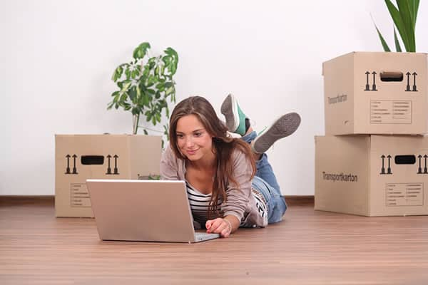 Woman on laptop with moving boxes
