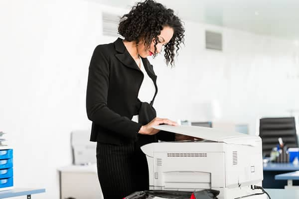 Business woman standing by copy machine